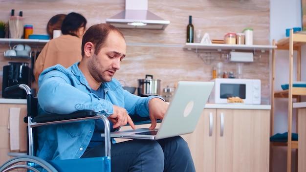 Empresário com deficiência em cadeira de rodas durante a chamada de vídeo no laptop na cozinha. esposa cozinhando a refeição. homem corporativo com paralisia, deficiência, deficiência, dificuldades para trabalhar após acidente tendo em