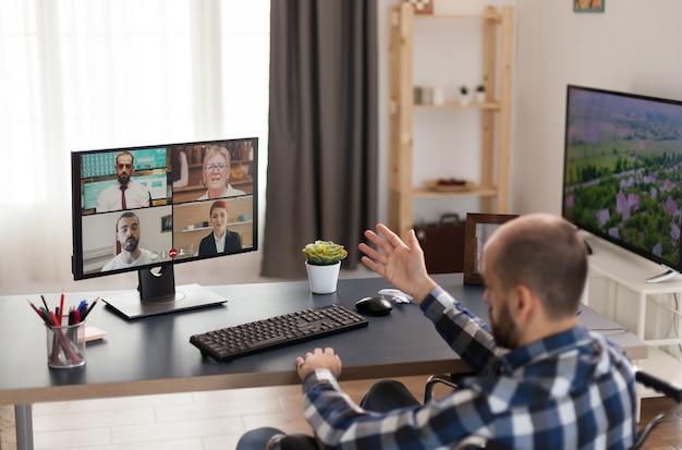 Empresário com deficiência em cadeira de rodas durante uma chamada de vídeo do escritório em casa. jovem freelancer imobilizado fazendo seu negócio online, usando alta tecnologia, sentado em seu apartamento, trabalhando remotamente em sp