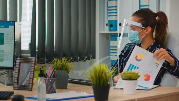 Empresário com deficiência, sentado em uma cadeira de rodas, usando proteção facial na prevenção de coronavírus, limpando as mãos antes de verificar os dados financeiros no escritório de negócios. freelancer respeitando a distância social