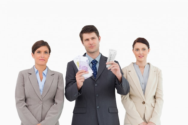 Empresário com dinheiro em pé entre os funcionários