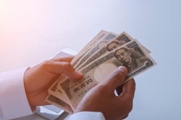 Empresário com dinheiro na mão, yen, investimento, sucesso e conceitos de negócio rentável.