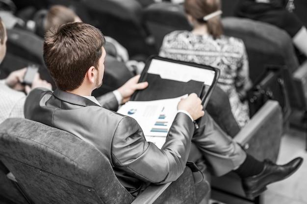 Empresário com documentos financeiros sentado na sala de aula