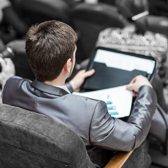 Empresário com documentos financeiros, sentado na sala de aula.