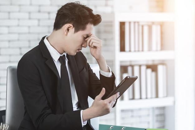 Empresário com dor de cabeça devido ao excesso de trabalho