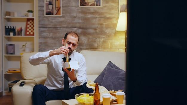 Empresário com gravata comendo macarrão sentado no sofá após um longo dia de trabalho. comida chinesa.