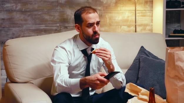 Empresário com gravata comendo um hambúrguer enquanto assiste tv. homem faminto.