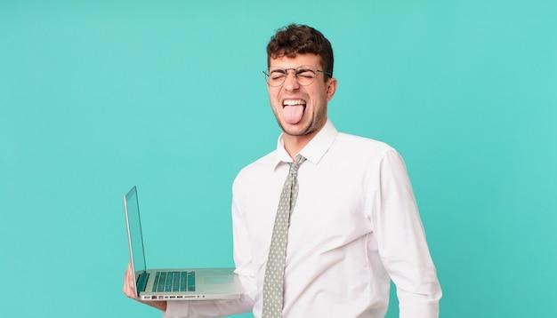 Empresário com laptop com atitude alegre, despreocupada, rebelde, brincando e mostrando a língua, se divertindo