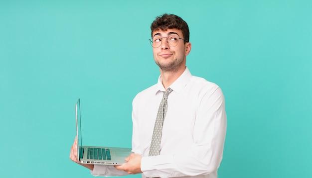 Empresário com laptop dando de ombros, sentindo-se confuso e incerto, duvidando com os braços cruzados e olhar perplexo