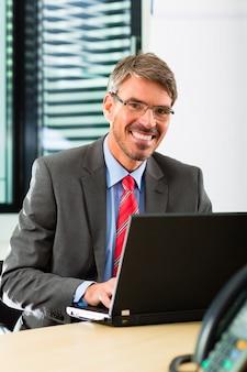 Empresário com laptop em seu escritório de negócios