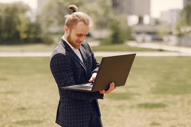 Empresário com laptop em uma cidade de verão