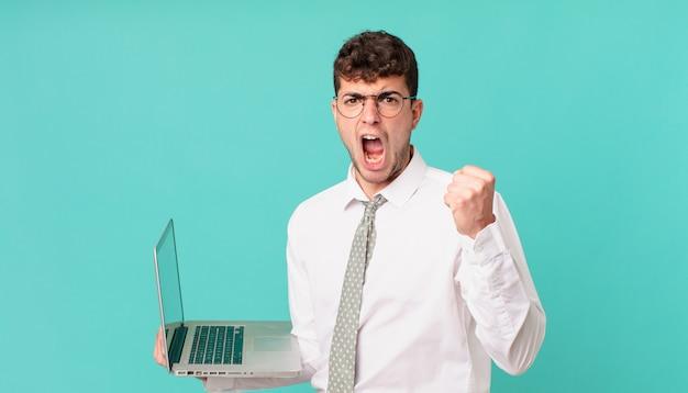 Empresário com laptop gritando agressivamente com uma expressão de raiva ou com os punhos cerrados celebrando o sucesso