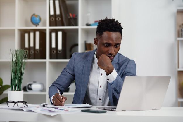 Empresário com laptop. jovem empresário africano está digitando algo no laptop em seu escritório.