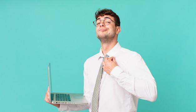 Empresário com laptop parecendo arrogante, bem-sucedido, positivo e orgulhoso, apontando para si mesmo