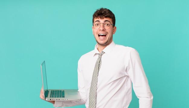 Empresário com laptop parecendo muito chocado ou surpreso, olhando com a boca aberta dizendo uau