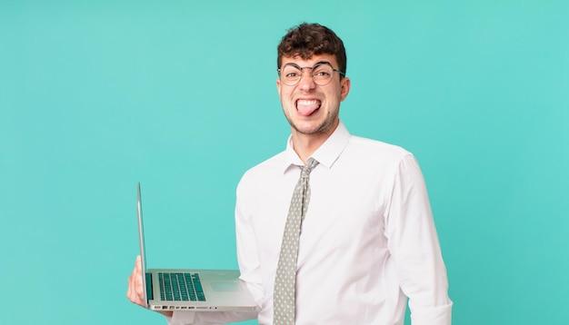Empresário com laptop se sentindo enojado e irritado, mostrando a língua, não gostando de algo desagradável e nojento