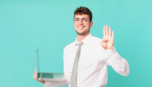 Empresário com laptop sorrindo e parecendo amigável, mostrando o número quatro ou o quarto com a mão para a frente, em contagem regressiva