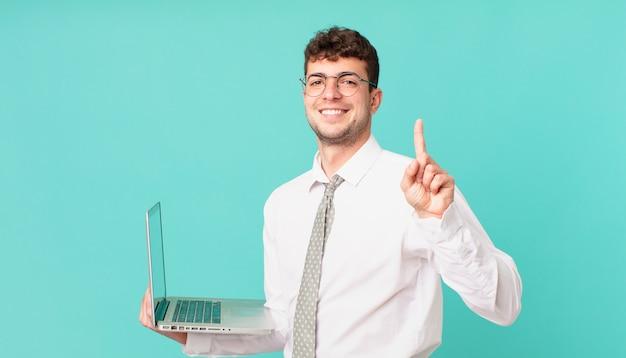 Empresário com laptop sorrindo e parecendo amigável, mostrando o número um ou primeiro com a mão para a frente, em contagem regressiva