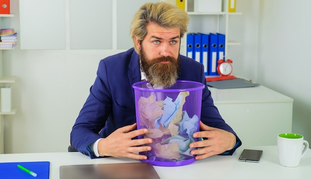 Empresário com lata de lixo. trabalhador de escritório com o cesto de lixo. homem barbudo procura documento perdido.