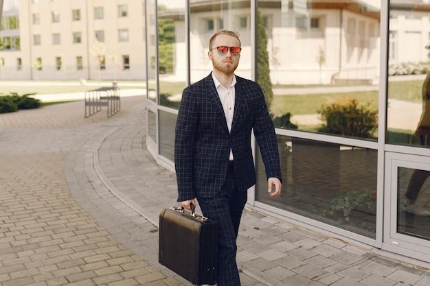 Empresário com mala caminhando por uma cidade de verão