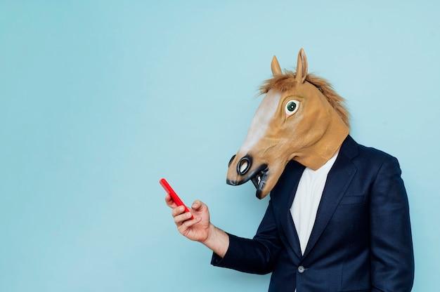 Empresário com máscara de cavalo usando smartphone