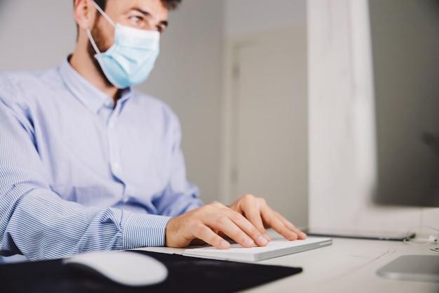 Empresário com máscara facial sentado em seu escritório e digitar o relatório durante o covid 19 surto.