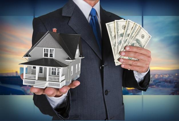 Empresário com mini casa e dólares americanos