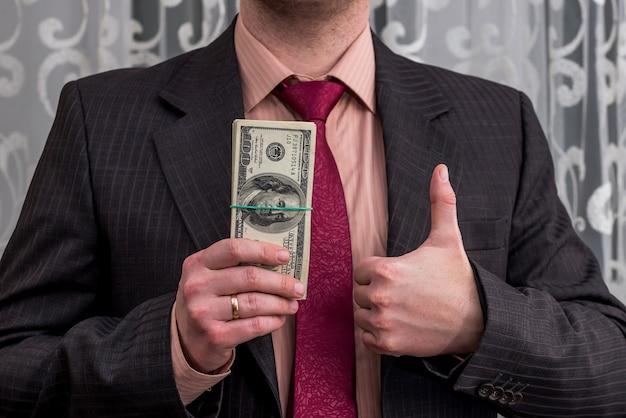 Empresário com notas de dólar em uma mão e polegar para cima