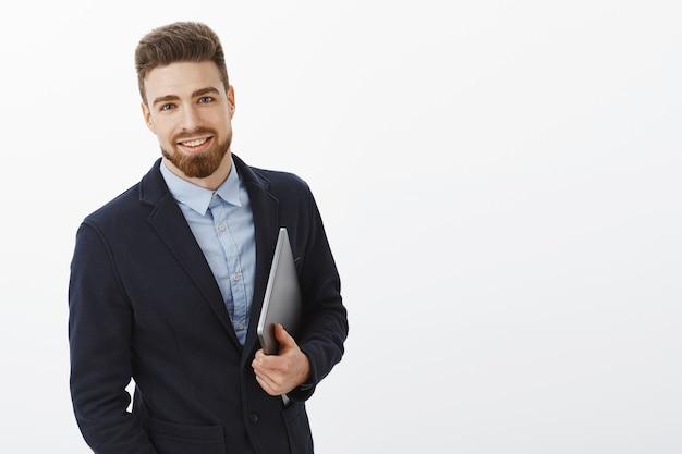 Empresário com olhos azuis e barba em pé, confiante em um terno formal, segurando o laptop na mão, olhando satisfeito e seguro, sendo ambicioso e bem-sucedido