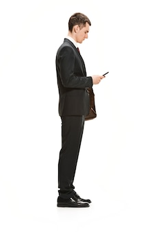 Empresário com pasta conversando no smartphone isolado na parede branca