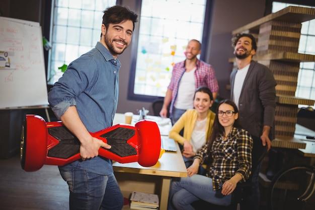 Empresário com placa auto-equilibrada enquanto colegas