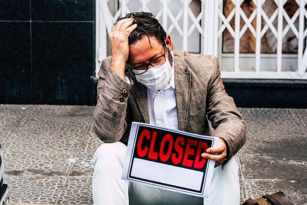 Empresário com placa fechada fora de sua loja devido à crise econômica do coronavírus