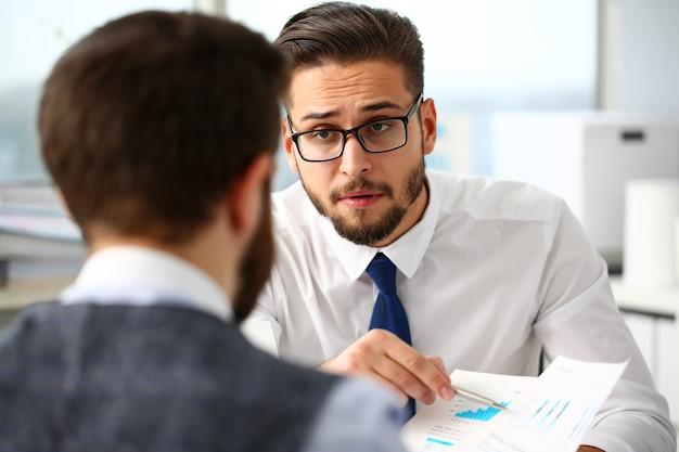 Empresário com quadro financeiro e caneta prata no braço resolve e discute o problema com o colega