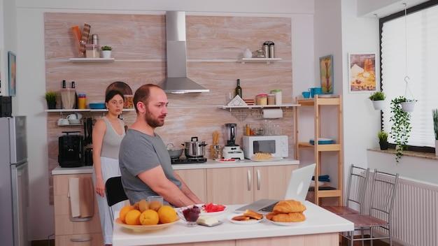 Empresário com raiva durante o café da manhã por causa de uma má notícia. freelancer infeliz, estressado, frustrado, furioso, negativo e chateado, de pijama, gritando durante a refeição matinal em casa. problemas de trabalho