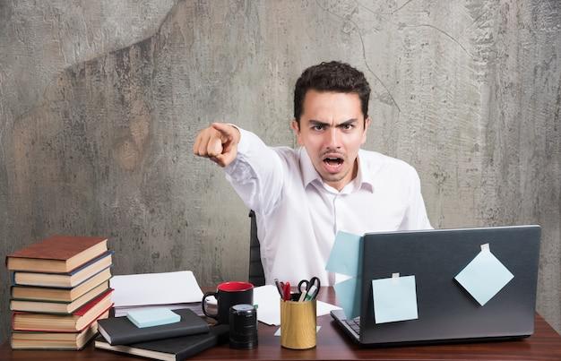 Empresário com raiva, falando com o telefone na mesa do escritório.