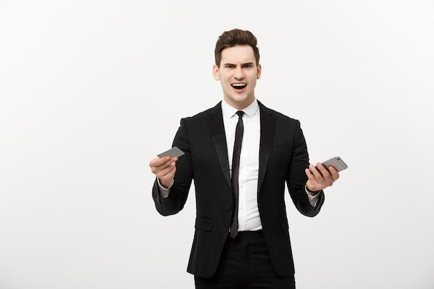Empresário com raiva segurando o cartão de crédito e o celular. enlouqueça enquanto faz compras online ou é um problema de negócios.