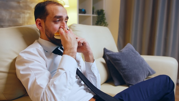 Empresário com roupa formal, sentado no sofá, comendo um hambúrguer e falando ao telefone após um dia cansativo.