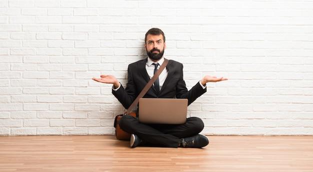 Empresário com seu laptop sentado no chão infeliz e frustrado com alguma coisa porque não entende algo