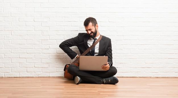Empresário com seu laptop sentado no chão, sofrendo de dor nas costas por ter feito um esforço