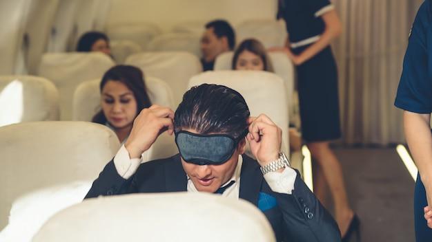 Empresário com sono viaja em uma viagem de negócios de avião. conceito de viajante executivo.