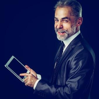 Empresário com tablet digital em fundo preto. a foto tem um espaço vazio para o seu texto