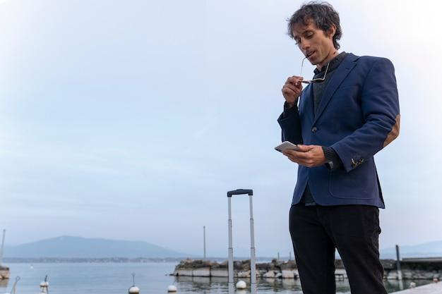 Empresário com telefone móvel no cais
