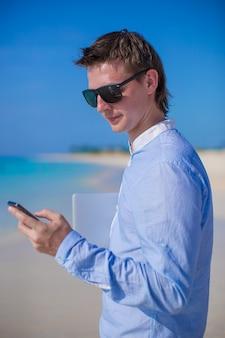 Empresário com telefone na mão em uma praia tropical