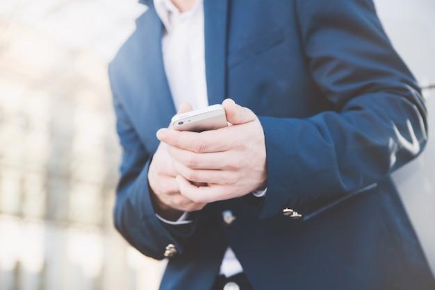 Empresário com telefone na mão.