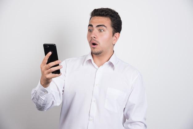 Empresário com telefone parecendo chocado com fundo branco.