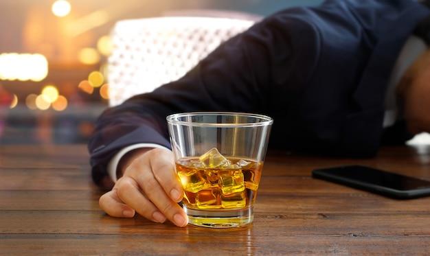 Empresário com uísque bourbon na mão, bêbado dormindo na mesa no pub