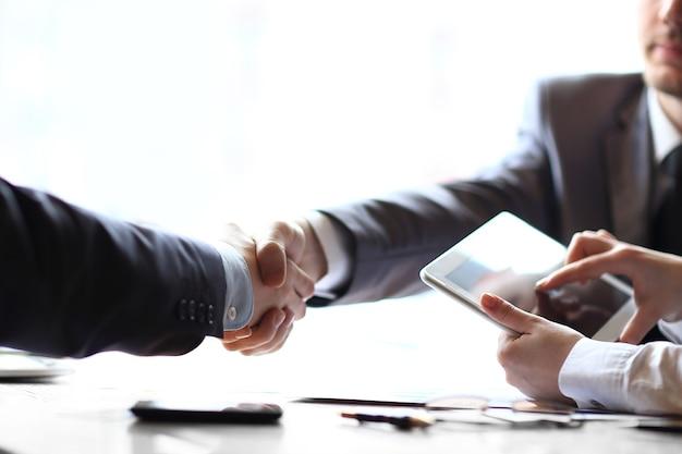 Empresário com um computador tablet no meio de um aperto de mão de parceiros de negócios