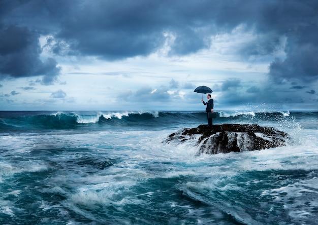 Empresário com um guarda-chuva em um oceano tempestuoso