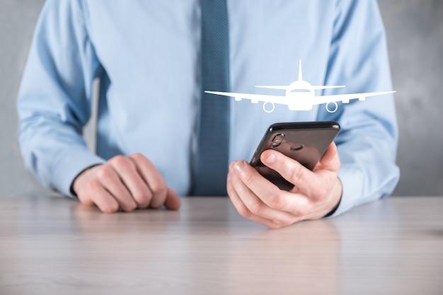 Empresário com um ícone de avião nas mãos. compra de bilhetes online. viagem.