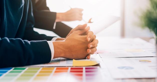 Empresário com um punhado na mesa que está ouvindo os resumos de trabalho de colegas de equipe, reunião de brainstorming e novo projeto de inicialização no local de trabalho.