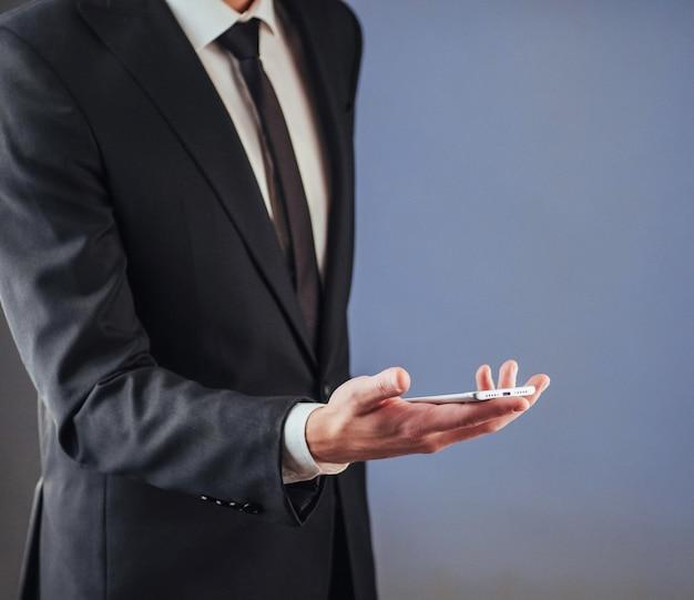 Empresário com um telefone na mão.